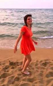 Lisa lachend in oranje jurk op het strand