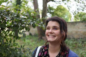Lisa staat in de kasteeltuin naast een struik